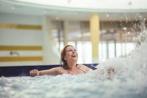 Eine Frau liegt im Massagebecken und lacht.